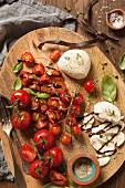 Gemischte Tomaten mit Mozzarella und Basilikum, schwarzer Pfeffer, Thymian und Balsamico auf Holzplatte