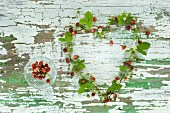 A heart made from wild strawberries, strawberry leaves and flowers on a wooden surface