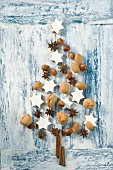 Cinnamon stars, cinnamon sticks, star anise and nuts in the shape of a Christmas tree