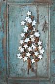 Cinnamon stars, cinnamon sticks, star anise and hazelnuts in the shape of a Christmas tree