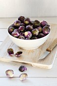 Fresh red Brussels sprouts in a bowl on a wooden chopping board