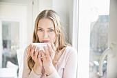 Blonde Frau hält Schale mit Kaffee in den Händen