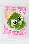 A white bread roll topped with wasabi leaves, wasabi Gouda and edible flowers
