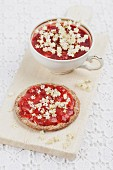 Homemade strawberry jam with elderflowers in a cup and on crispbread