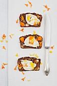 Drei Scheiben selbstgebackenes Ingwer-Brot mit Frischkäse und Ringelblüten