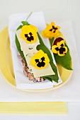 Brotscheibe belegt mit Käse, Bärlauchblatt und Stiefmütterchenblüten