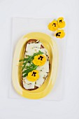 A slice of bread topped with Pecorino cheese, rocket and pansies