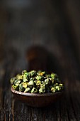 Green peppercorns on a wooden spoon (close-up)