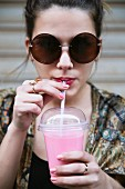 A young woman wearing sunglasses drinking a smoothie from a plastic cup