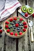 A green smoothie bowl with kiwis, raspberries, blueberries and chia seeds