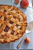A whole peach pie with a lattice lid