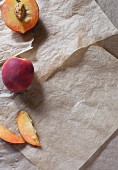 Fresh peaches, whole, halved and sliced (seen from above)