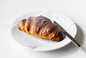 A croissant on a white plate with a knife