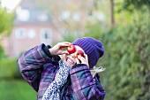 Kleines Mädchen in Winterkleidung bedeckt ihre Augen mit zwei Äpfeln