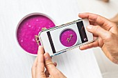A woman using a smartphone to take a picture of a dragon fruit smoothie bowl