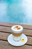 A latte backyard in a glass on a wooden table by a pool