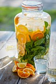 Homemade orangeade with orange slices and mint in a preserving jar