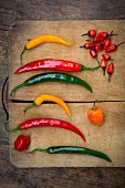 Various chilli peppers on a wooden chopping board (seen from above)