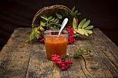 A jar of rowan berry jam with a wicker basket of rowan berries in the background