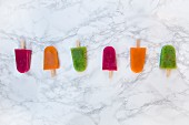 Various fruit ice lollies in a row on a marble surface