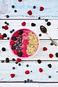 A smoothie bowl with berries and hemp seeds on a wooden surface (seen above)