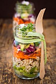 Springtime layered salads in glasses with rice, vegetables and daisies