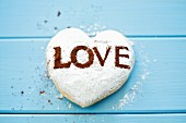 A heart-shaped doughnut with the word 'Love' in cocoa powder on the blue wooden surface