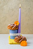 Two mini wreath cakes decorated with a burning candle and marigolds