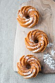 Three mini cakes wreath dusted with icing sugar on a wooden board