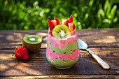 A glass of chia pudding with kiwi and strawberries on a table outside