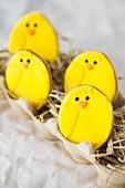Gelbe Osterküken-Plätzchen auf Stroh