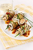Aubergine rolls filled with fish in a tomato oil