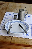 A rustic place setting with a pewter beer tankard