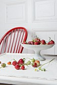 Strawberries and a porcelain bowl on a wooden table with a white wooden door and a red wooden chair in the background