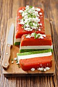 Tri-coloured terrine with tomatoes, cream cheese and green peas topped with feta cheese