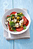 Caprese salad with buffalo mozzarella, olives and pesto