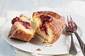 A doughnut muffin with raspberry jam, sliced