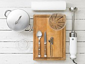 Kitchen utensils: a pot, a citrus juicer, cutlery, a measuring jug and a hand blender