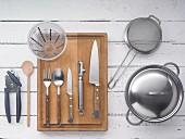 Küchenutensilien: Topf, Sieb, Messer, Besteck, Messbecher und Dosenöffner