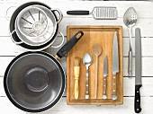 Kitchen utensils: a pan, pots, a grater, a draining spoon and knives