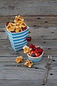 Waffle bites in a paper bag with cherries and berries