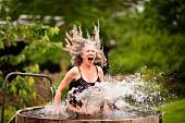 Ältere Frau im Badeanzug springt in Wasserbottich im Garten