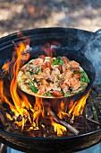 Lachspizza wird in einer Pfanne auf offenem Feuer gebacken