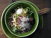 Spaghetti with an onion and olive sauce and rocket