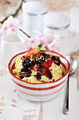 Millet pudding with pecan nuts and a strawberry and blueberry sauce