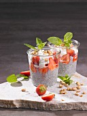 Chia seed puddings with strawberries, yoghurt, nuts and mint