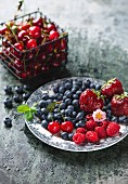 Fresh berries on a plate and sour cherries in a wire basket