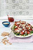 Salad with strawberries, bacon, pearl beans, feta cheese, vegetables and strawberry sauce