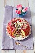 Lemon cake with red icing and colourful Easter eggs