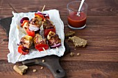 Chicken kebabs with pineapple, bacon, red peppers and onions